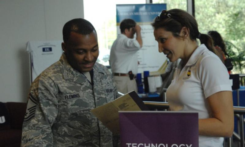 Senior Master Sgt. Rashaun Fleming, of the 20th Operations Support Squadron, speaks with Kathryn Looney of San Diego's Ashford University during an education fair at Shaw Air Force Base, S.C., in October 2012. Government officials have found little evidence of student loan servicers unlawfully charging active-duty servicemembers high interest rates on student loans. (U.S. Air Force)