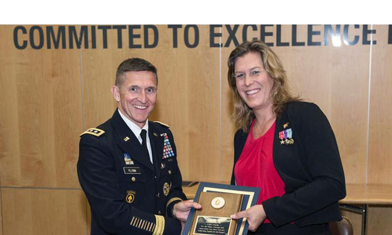 Retired Navy SEAL Kristin Beck, born Christopher T. Beck, receives a plaque from DIA Director Lt. Gen. Michael Flynn following the agency's Pride Month event June 18, 2014. (DIA Public Affairs)
