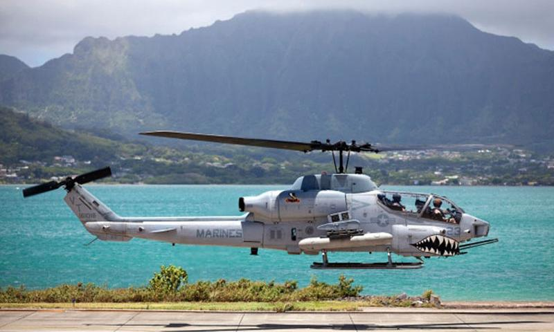 An AH-1W Super Cobra helicopter departs the Marine Corps Air Station Kaneohe Bay, Hawaii, flightline on a maintenance and readiness flight, June 13, 2013. (Photo by U.S. Marines)