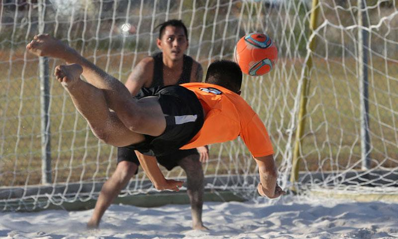Crushers FC's Justin Samonte gets airborne for a diving header for goal as Strykers FC goalkeeper Andre Gadia tracks the ball in a Week 2 Land Shark Beach Soccer League match at the Guam Football Association National Training Center beach soccer court.
