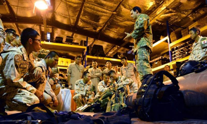 An U.S. Air Force pararescueman explains some of the equipment used during missions to visiting members of the Japan Self Defense Forces' Deployment Air Force for Counter-Piracy Enforcement at Camp Lemonnier, Djibouti, Dec. 3, 2013. (CHAD THOMPSON/U.S. AIR FORCE)
