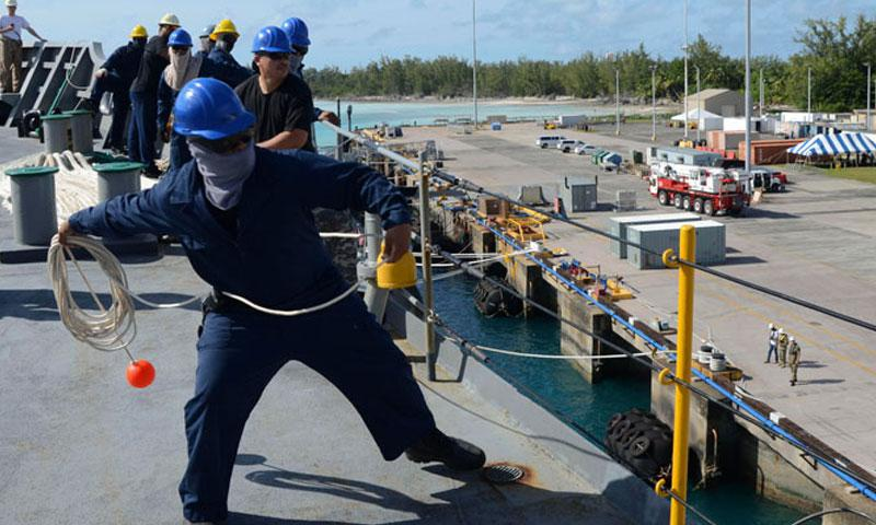 DIEGO GARCIA, British Indian Ocean Territory (July 8, 2016) A Civilian mariner attached to Military Sealift Command aboard the submarine tender USS Frank Cable (AS 40), bring in a line from a tug boat to prepare to dock in Diego Garcia, July 8. (U.S. Navy Photo by Mass Communication Specialist Seaman Josh Coté/Released)