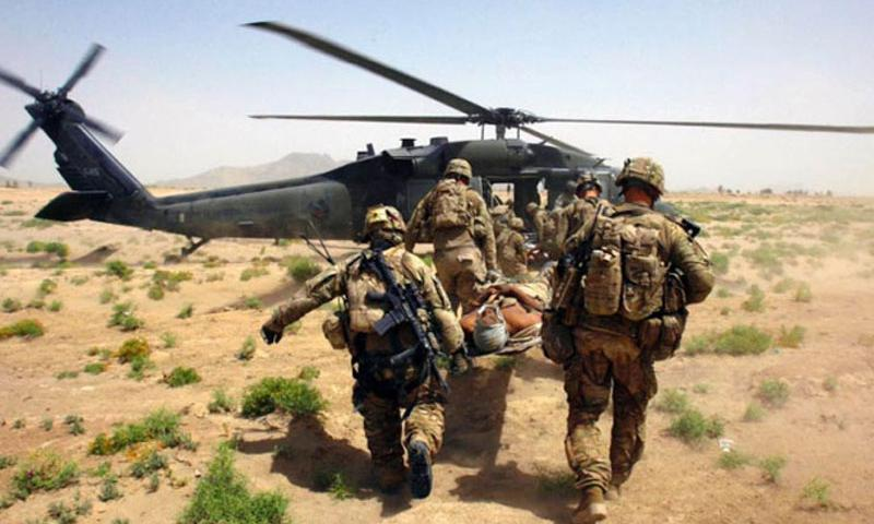 U.S. troops carry a wounded soldier, injured by an improvised explosive device in Afghanistan, to a helicopter on June, 15, 2011. (Photo by Stars and Stripes)