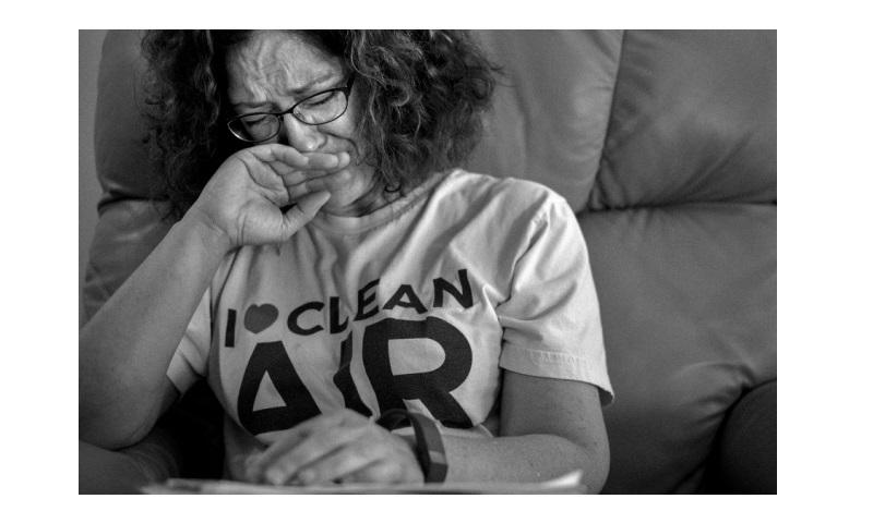 Devawn Bledsoe, a local activist who has taken up a campaign to stop the open burns and who suffered from a thyroid disease she blames on the pollution, cries while she goes through papers outlining the issue at her home in Blacksburg, Va., on May 28, 2017. (ASHLEY GILBERTSON/VII PHOTO FOR PROPUBLICA)