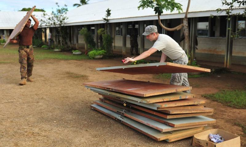 Airman 1st Class Devin Laird, places an old door on the pile at Neiafu Government Primary School, Neiafu, Vava'u, Tonga, on July 17, 2014. Military electricians, structural craftsmen, carpenters and plumbers are working to fix up the school as part of the Pacific Angel exercise. Laird is deployed from the 374th Civil Engineer Squadron, Yokota Air Base, Japan. (RACHELLE COLEMAN/U.S. AIR FORCE)
