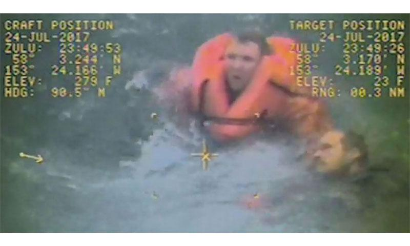 Coast Guard video of one of the rescues shows the captain in an orange life vest swimming to a man struggling to stay afloat and pulling him to an awaiting boat. (U.S. COAST GUARD)