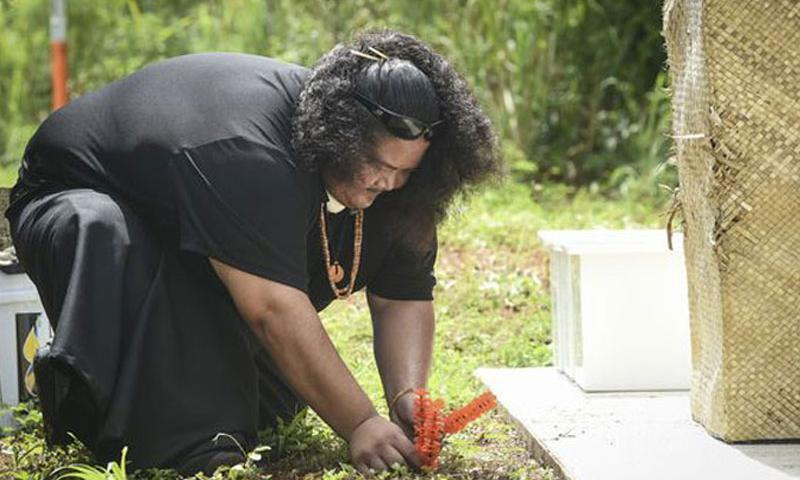 Jeremy Cepeda, of the I Fanlalai'an oral history project, plants a ceremonial niyoron, or orange blossom at the Dandan Reburial Memorial in Inarajan, Guam, on July 17.  The remains of approximately 10 ancient Chamorros were laid to rest after being discovered during a road widening project in 2010. (Photo by Mark Scott, Pacific Daily News via AP)