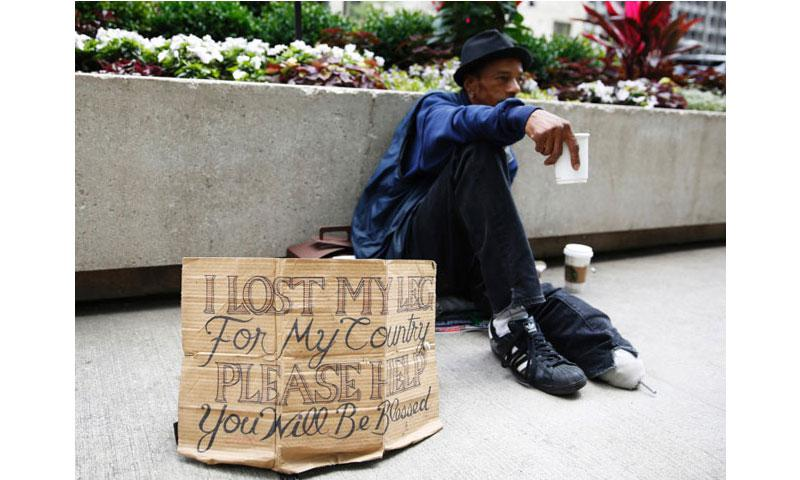 A homeless veteran displays a redesigned cardboard sign in downtown Chicago on July 2, 2015. (Michael Noble Jr., Chicago Tribune/TNS)