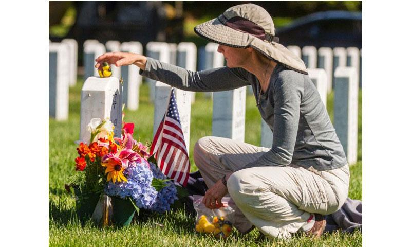 Alison Malachowski tends to the grave of her son, U.S. Marine Corps Staff Sgt. James Malachowski, in Section 60 of Arlington National Cemetery, July 22, 2015. Staff Sgt. Malachowski was killed by an improvised explosive device in Afghanistan during his fourth combat deployment on March 20, 2011. (Ken Scar/U.S. Army)