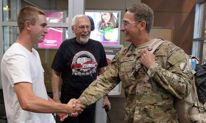 "In a 2015 file photo, three generations of North Dakota Air National Guard members get together at Hector International Airport in Fargo. Master Sgt. Scot Gordon, right, is greeted by his father, retired Lt. Col. Earl ""Shell"" Gordon, center, and his son, Airman 1st Class Trevor Gordon upon Scot's return from a six-month deployment to Afghanistan. (David H. Lipp/Air National Guard)"