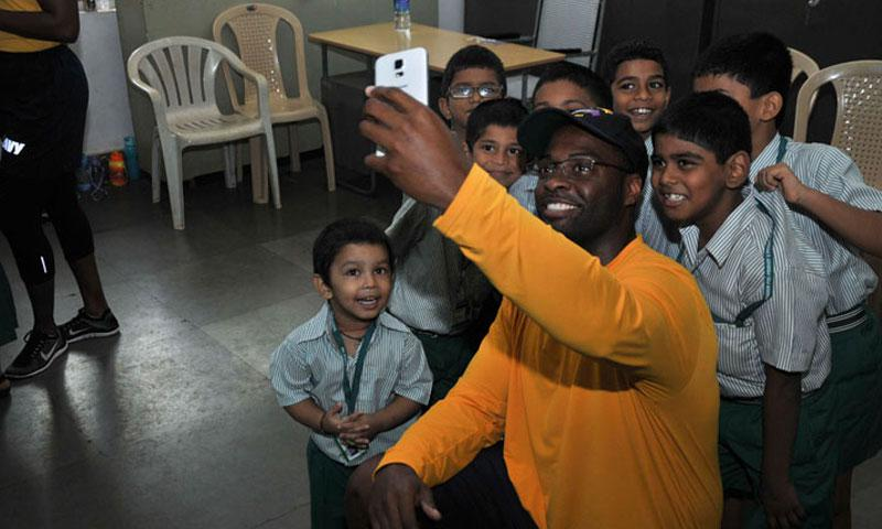 GOA, India (August 1, 2016) Hull Maintenance Technician 1st Class Antuan Mills, a native of Cleveland, assigned to the submarine tender USS Frank Cable (AS 40), poses for a photo with children during a Community Relations event at the Bal Bhavan children's home, Aug. 1. (U.S. Navy Photo by Mass Communication Specialist Seaman Josh Coté/Released)