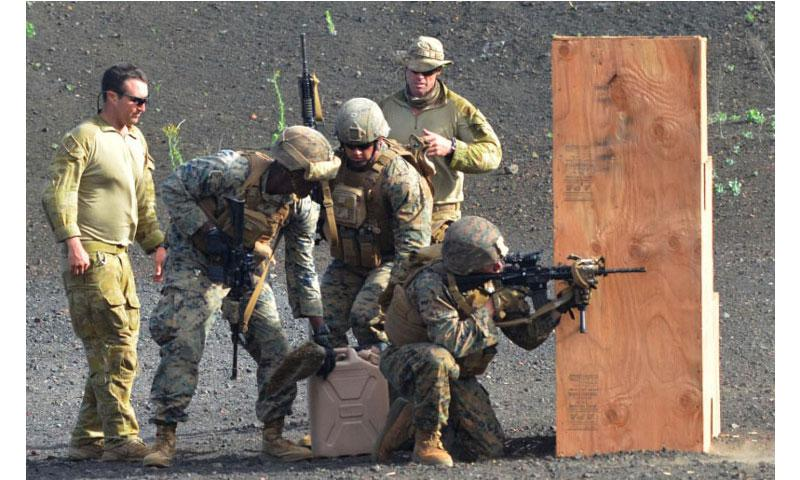 Marines compete in a timed marksmanship competition at Pohakuloa Training Area, Hawaii, during RIMPAC 2016, as two Australian soldiers monitor the event. (Wyatt Olson/Stars and Stripes)