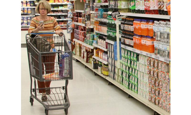 A patron checks her smartphone while shopping at the Fort Belvoir, Va., commissary in April, 2015. (DeCA)
