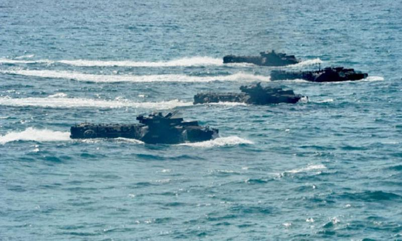 Troops steer amphibious assault vehicles toward shore during a simulated beach assault during Rim of the Pacific Exercise 2014 in July. Japan is working with U.S. Marines to build its own amphibious force. (Corey T. Jones/U.S. Navy)