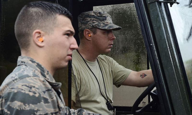 Senior Airman Brian Fish (left), listens to Airman 1st Class Jack Mowery (right), both 36th Munitions Squadron Material Flight storage crew members, as he explains where to drop a pallet of guidance controlled units July 30, 2014, on Andersen Air Force Base, Guam. (U.S. Air Force photo by Staff Sgt. Robert Hicks/Released)