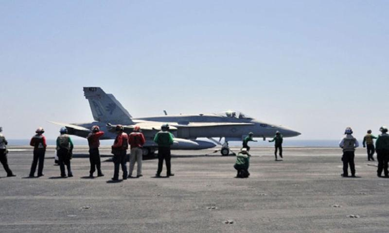 Sailors make final inspections on an F/A-18C Hornet assigned to the Golden Warriors of Strike Fighter Squadron 87 aboard the USS George H.W. Bush, on Aug. 7, 2014. (Margaret Keith/U.S. Navy)