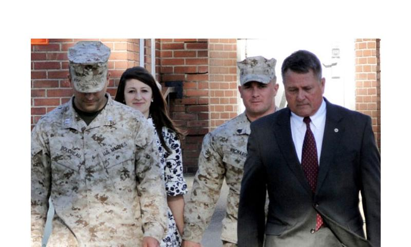 U.S. Marine Corps Sgt. Robert Richards, at right in rear, with his wife Raechel Richards, follow his military attorney and defense lawyer Guy Womack out of the courtroom at Camp Lejeune, N.C., on March 19, 2013. Sgt. Richards was found dead at his Jacksonville, North Carolina home on Wednesday. (Jennifer Hlad/Stars and Stripes)