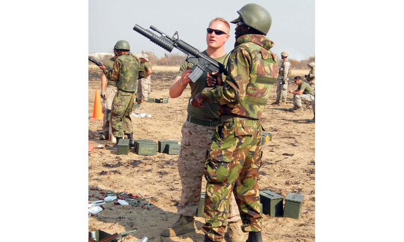 Marine Corps Cpl. Aaron Bohlen helps a Botswanan soldier fire a non-lethal weapon at a range at Thebephatshwa Air Base, Botswana, during Southern Accord 12. DOD photo by Donna Miles