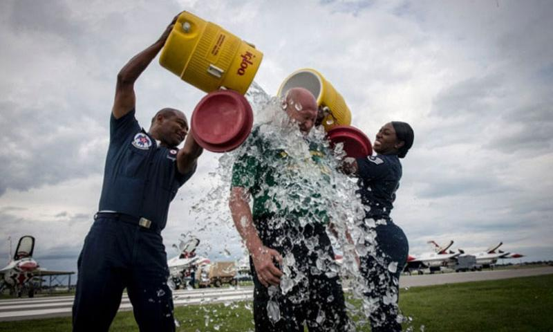 Air Force Staff Sgt. Francisco Garrigas and Staff Sgt. Kristina Overton dump buckets of ice water on Pete Lawrence during an ice bucket challenge in Rochester, N.Y., Aug. 14, 2014. The challenge is a viral movement designed to raise awareness for Amyotrophic lateral sclerosis, also known as ALS or Lou Gehrigs' disease. (Manuel J. Martinez/U.S. Air Force)