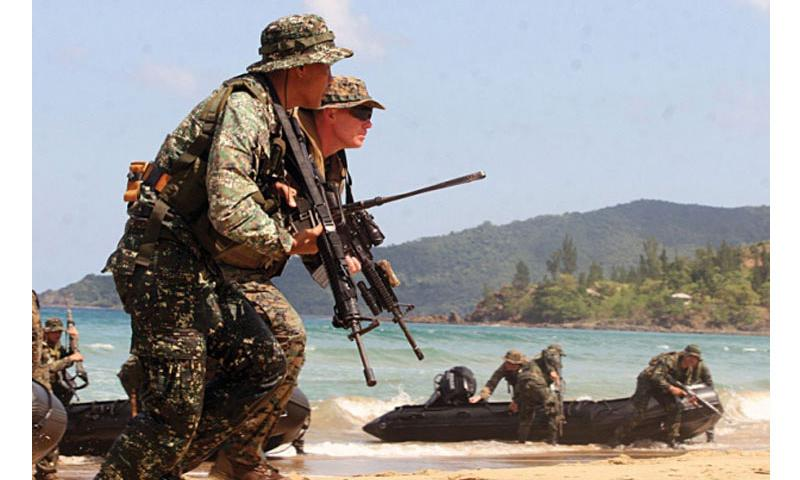 Marines from the 3rd Marine Expeditionary Brigade, headquartered in Okinawa, storm a beach in the Philippines during a 2011 exercise. Sen. John McCain, R-Ariz., said Aug. 21, 2013,during a visit to the Pacific theater that Congress still has concerns over the planning and costs of moving Marines off Okinawa. (Courtesy of the U.S. Marine Corp)