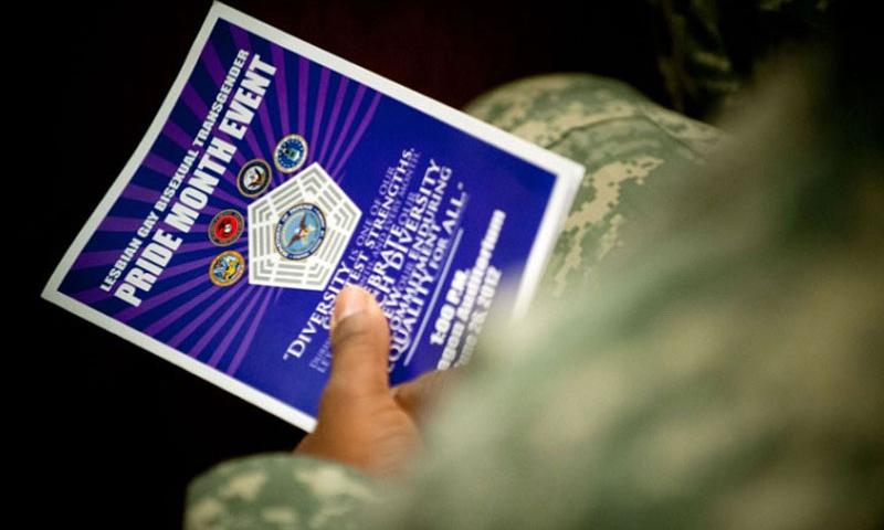 A servicemember holds a leaflet during Lesbian, Gay, Bisexual and Transgender Pride Month at the Pentagon in June 2012. The Pentagon's ban on transgender troops would end May 27 under a draft timeline on repeal of the policy. (Chad McNeeley/U.S. Navy)