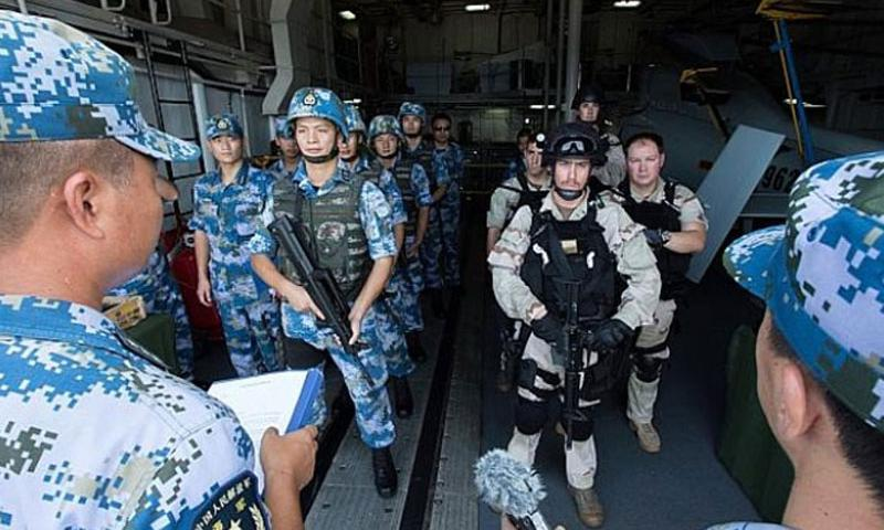Chinese sailors and U.S. sailors with a search-and-seizure team from the guided-missile destroyer USS Mason get final instructions before participating in a small-arms exercise aboard the Chinese destroyer Harbin in the Gulf of Aden on Saturday, Aug. 24, 2013. (Rob Aylward/ Courtesy of the U.S. Navy)
