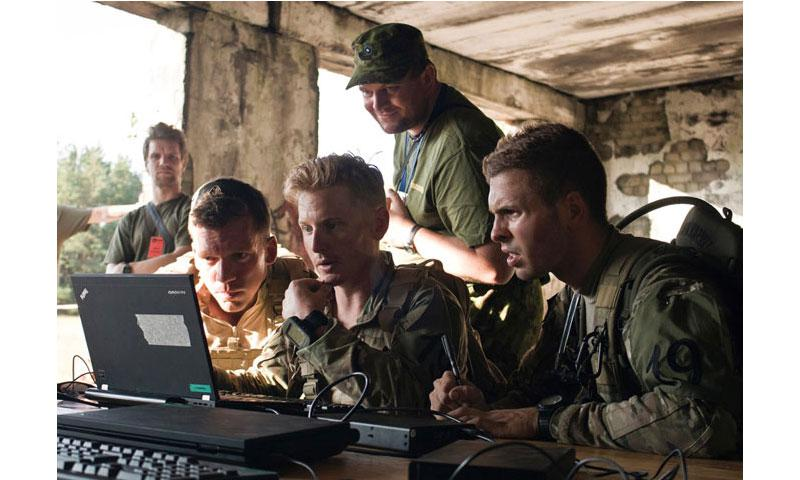 Evaluators from the Estonian Defense League observe soldiers attached to a Long Range Surveillance team as they search for relevant files on a laptop staged at the Cyber Challenge checkpoint during an exercise near Tapa, Estonia, on Aug. 8, 2015. (U.S. Army)