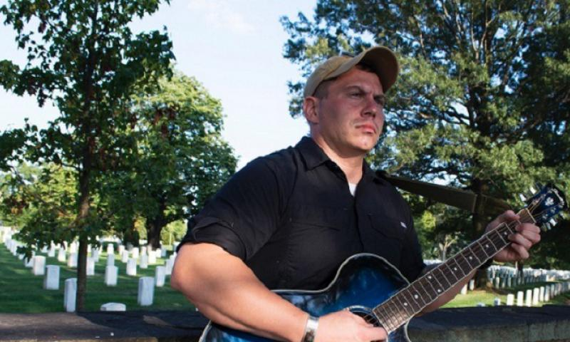 Staff Sgt. Nathan Fair strums his guitar in Fort Myer, just outside Arlington National Cemetery, in late August 2014. (Meredith Tibbetts/Stars and Stripes)