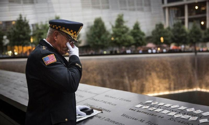 Sam Pulia, mayor of Westchester, Ill., and a former police officer of the same town, mourns over the name of his cousin, New York firefighter Thomas Anthony Casoria prior to the memorial observances held at the site of the World Trade Center in New York, on Thursday, Sept. 11, 2014. Casoria was killed in the South Tower in the attacks of Sept. 11, 2001. (Andrew Burton, Pool/AP)