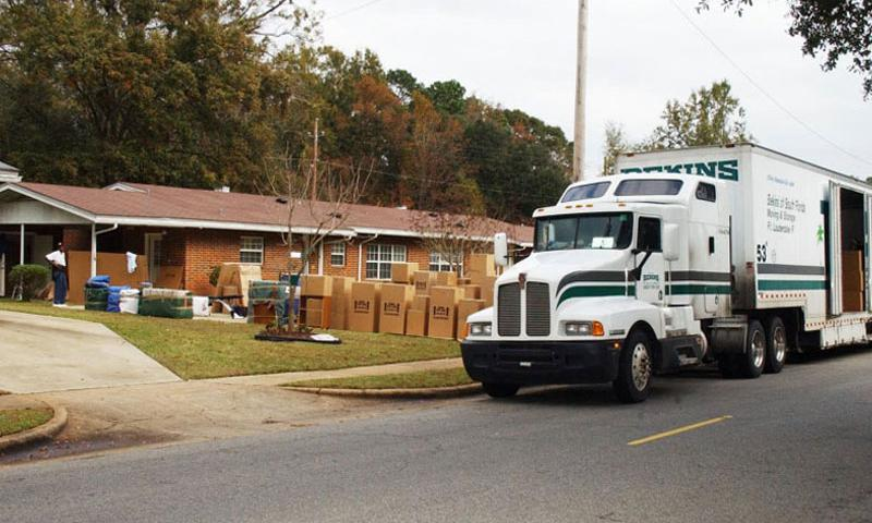 A moving truck is unloaded as a family moves into their new home. (Department of Defense)