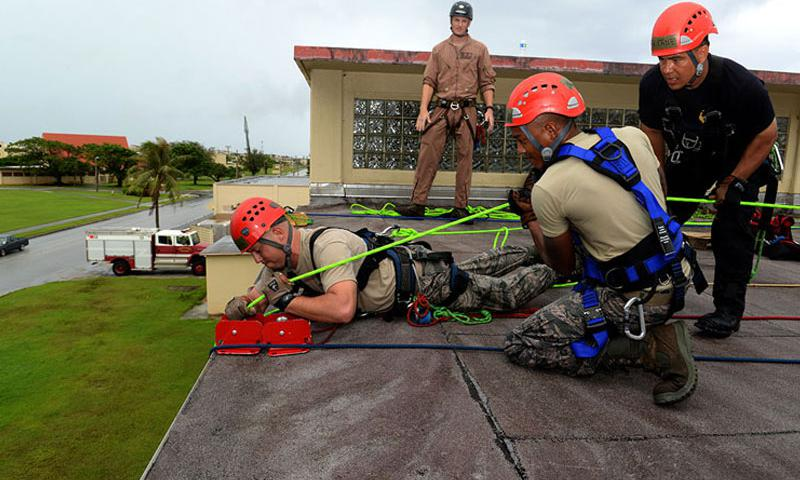 Master Sgt. Jason Berry, 554th RED HORSE Squadron fire and emergency services superintendent (right,) supervises Andersen Air Force Base and Naval Base Guam firefighters secure a simulated victim on the roof of the Hot Spot during the Department of Defense Rescue Technician course event Sept. 16th, 2014, on Andersen. (U.S. Air Force photo by Tech. Sgt. Zachary Wilson/Released.)