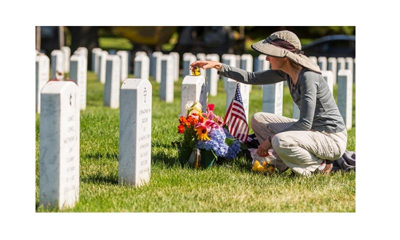 Alison Malachowski tends to the grave of her son, U.S. Marine Corps Staff Sgt. James Malachowski, in Section 60 of Arlington National Cemetery. Staff Sgt. Malachowski was killed by an IED during his fourth combat deployment on March 20, 2011, while his unit was raising the Afghanistan national flag over a small compound near Patrol Base Dakota in Marjah Province. (Army photo by Sgt. Ken Scar)