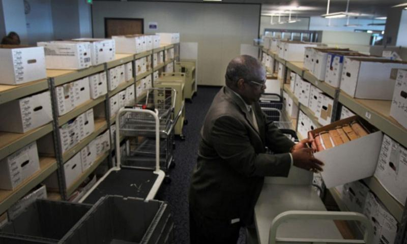 Douglas Bragg, the director of the Veterans Benefits Administration office in Oakland, Calif., looks into one of the many boxes that contain the cases of veterans with pending claims, April 18, 2013. (Rick Loomis, Los Angeles Times/MCT)