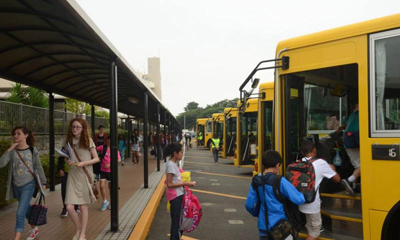 "Students from Yokosuka Middle School at Yokosuka Naval Base, Japan, head toward their school buses after the first day of classes, Monday, Aug. 31, 2015. The union representing about 2,000 Department of Defense Education Activity Pacific teachers has appealed to DODEA headquarters for help fixing what it called a ""broken system,"" saying some teachers have gone unpaid or without base ID cards. (Tyler Hlavac/Stars and Stripes)"