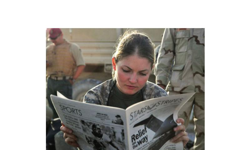 In a 2009 file photo, First Lt. Tracy Tyson from Seattle, Wash., assigned to the 5th Brigade 2nd Infantry Division reads Stars and Stripes in Kandahar Airfield, Afghanistan, while waiting for a flight to Forward Observation Base Wolverine. (Photo by U.S. Navy)
