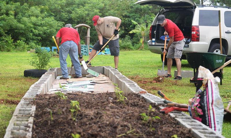 Airmen assigned with the 554th RED HORSE expand a garden Sept. 26, 2015, at the Guma San Jose Homeless Shelter, Dededo, Guam. The team offered specialized services to assist with the shelter's electrical, plumbing and air conditioning issues. Crews also expanded a garden to allow residents to grow their own fruits and vegetables and develop healthy eating habits. (U.S. Air Force photo by Senior Airman Joshua Smoot/Released)