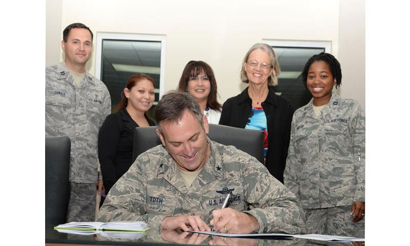 Brig. Gen. Andrew Toth, 36th Wing commander, signs the Domestic Violence Awareness Month proclamation Sept. 30, 2014, on Andersen Air Force Base, Guam. The Family Advocacy Program staff briefed wing leadership on upcoming events to be held throughout the month. (U.S. Air Force photo by Tech. Sgt. Zachary Wilson/Released)