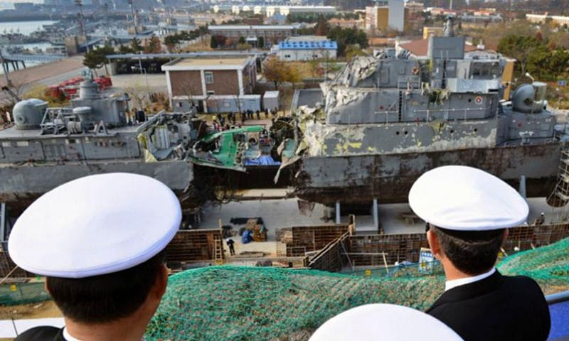 "U.S. and South Korean officials look at the remains of the Republic of Korea ship Cheonan while touring a port facility in Pyeongtaek on Nov. 22, 2013. The Pohang-class corvette was sunk by a North Korean torpedo on March 26, 2010. The sinking of the Cheonan is an example of so-called ""gray-zone"" incidents, which can't be defined as purely military contingencies and thefore create quandaries on how to respond. (Joshua Bryce Bruns/U.S. Navy)"