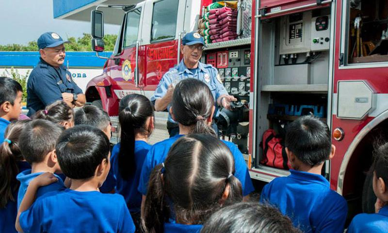 U.S. Naval Base Guam Fire and Emergency Services Fire Captain James Ballesta gives students a tour of a fire truck at M.U. Lujan Elementary School in Yona, Oct. 10. The presentation was made in observance of Fire Prevention Week. (U.S. Navy photo by Shaina Marie Santos/Released)