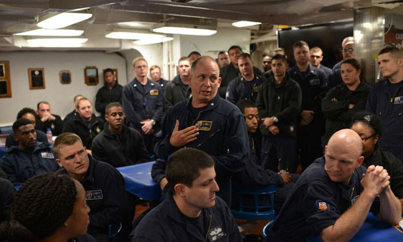 "Cmdr. Ken Pickard, commanding officer of the guided-missile destroyer USS Carney, speaks to crewmembers in the mess hall on Sept. 23, 2015. Pickard is wearing ""flyers coveralls,"" one of two new flame-resistant sets of coveralls being tested by the Navy aboard the Carney. Several sailors behind Pickard can be seen wearing traditional utility coveralls. (Steven Beardsley/Stars and Stripes)"
