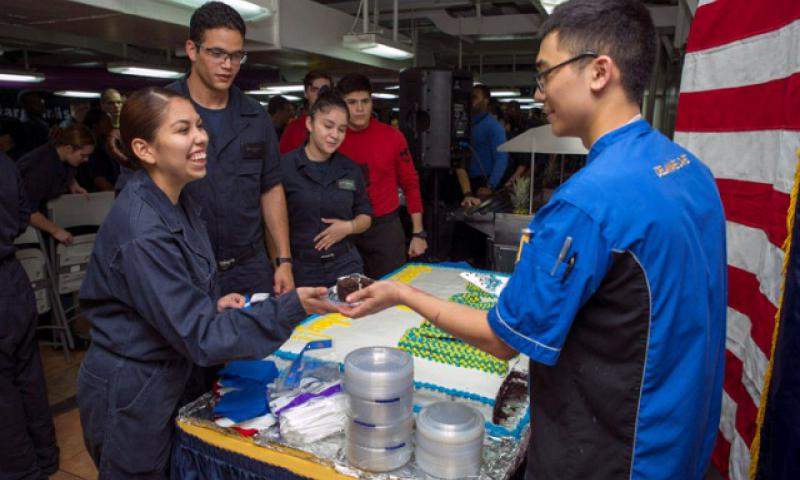 Culinary Specialist Seaman John Bona, from Sacramento, Calif., right, serves cake to Sailors during the 239th Navy Birthday Celebration aboard the Nimitz-class aircraft carrier USS George Washington (CVN 73). (U.S. Navy photo by Mass Communication Specialist 3rd Class Chris Cavagnaro)