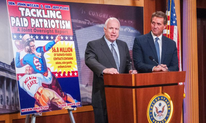 Arizona's two Republican Senators John McCain and Jeff Flake stand beside a billboard advertising the results of an investigative report questioning a Defense Department marketing program that doles out millions of dollars to various professional sports league teams to pay for patriotic tributes at games during a press event on Capitol Hill on Wednesday, Nov. 4, 2015. (Carlos Bongioanni/Stars and Stripes)
