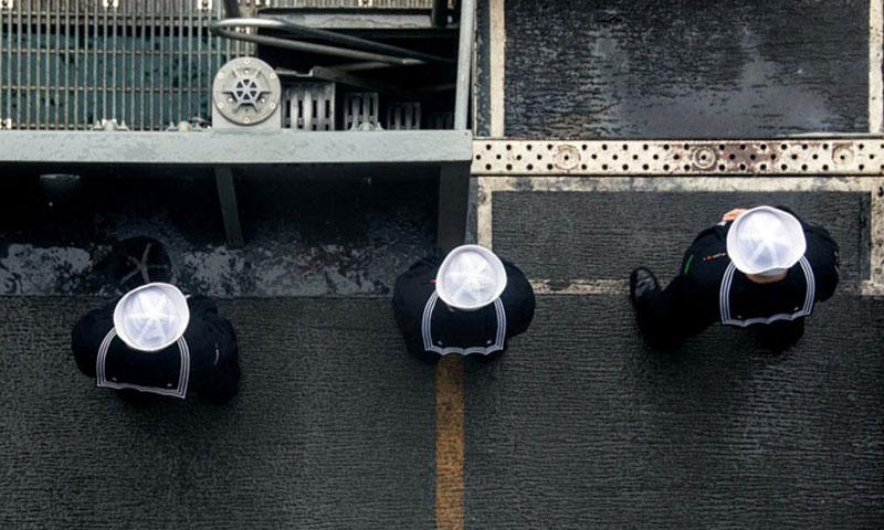 Sailors man the rails on the flight deck of the USS Ronald Reagan as the ship pulls into Busan, South Korea, for a port visit, Oct. 16, 2016. The Navy has issued preliminary guidance for issues arising from sailors seeking gender transition, noting that no changes will made to the service's physical readiness program for those individuals. (Kenneth Abbate/U.S. Navy)