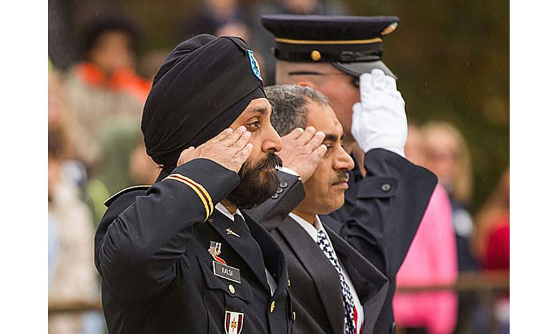 Maj. Kamal S. Kalsi, left, participates in a solemn salute to fallen soldiers at the Tomb of the Unknown Soldier at Arlington National Cemetery on Monday. (Russell Brammer/Sikh Coalition)