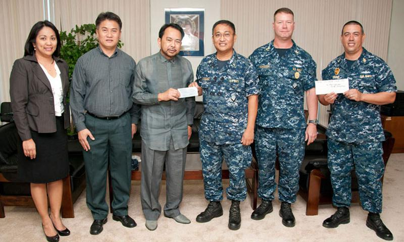 U.S. Naval Base Guam (NBG) Chaplain Lt. Cmdr. Rean Enriquez presents a check to Philippine Consul General Bayani Mangibin at the Philippine Consulate General Office in Tamuning, Guam Nov. 19. The chapel's donation of $3,187 will go to the Philippine Red Cross to support relief efforts following Super Typhoon Haiyan. The Chief Petty Officer Association from USS Frank Cable (AS 40) also donated more than $1,165 for relief efforts. (U.S. Navy photo by Jesse Leon Guerrero/Released)