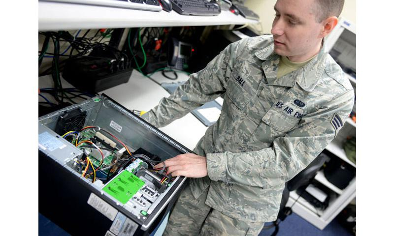 Senior Airman Chris Ball, 36th Communications Squadron client system technician, fixes an incorrectly installed heat sync, Nov. 19, 2014 on Andersen Air Force Base, Guam. The 36th CS won the Air Force Information Dominance Small Unit Award for best communication squadron at the major command level for 2014. (U.S. Air Force photo by Staff Sgt. Robert Hicks/Released)