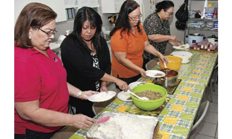 Serving the Community: From left: Lorraine Unpingco, Natti Pisaro, Winnie Camacho and June Concepcion  from Naval Facilities and Engineering Command (NAVFAC) Marianas plate a feast at the Kusinan Kamalen Karidat in Hagatna Nov. 6. The group from NAVFAC Marianas, called the Sisters in Christ, volunteer monthly at the facility, feeding dozens of fellow community members. U.S. Navy photo by Shaina Marie Santos/Released