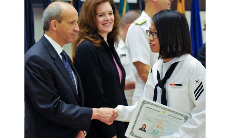 Ship's Serviceman Jiandan Zhu, attached to the USS Blue Ridge, receives a certificate of citizenship during a naturalization ceremony at Yokosuka Naval Base, Japan, Sept. 17, 2015. Forty men and women from 18 different countries recited the Oath of Allegiance and obtained U.S citizenship. (Don Patton/U.S. Navy)
