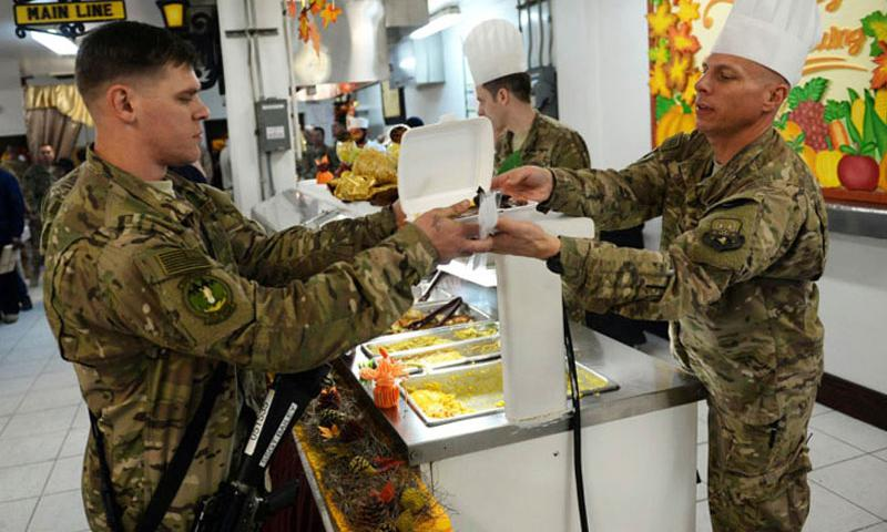 American troops dish out a Thanksgiving Day meal at Bagram Air Field in Afghanistan on Thursday, Nov. 27, 2015. Nearly 10,000 American servicemembers remain in the country. (Josh Smith/Stars and Stripes)