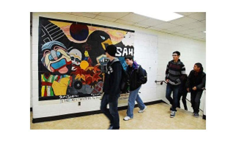 Students at Seoul American High School walk past a mural that may soon be replaced with a newer mural. That possibility has prompted an outcry from students and alumni who say it is a unifying symbol for past and current students. (Photo by Ashley Rowland/Stars and Stripes)